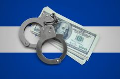 Honduras flag with handcuffs and a bundle of dollars. Currency corruption in the country. Financial crimes.  royalty free stock image
