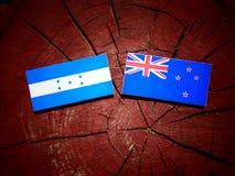 Honduras flag with New Zealand flag on a tree stump isolated. Honduras flag with New Zealand flag on a tree stump royalty free stock photos