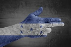 Honduras flag painted on male hand like a gun. Isolated on concrete royalty free stock photo