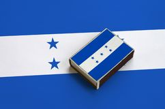 Honduras flag is pictured on a matchbox that lies on a large flag.  royalty free stock photography