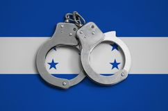 Honduras flag and police handcuffs. The concept of observance of the law in the country and protection from crime.  stock images