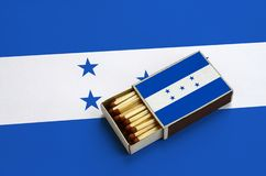 Honduras flag is shown in an open matchbox, which is filled with matches and lies on a large flag.  stock photo