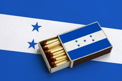 Honduras flag is shown in an open matchbox, which is filled with matches and lies on a large flag.  stock photos
