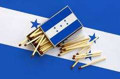 Honduras flag is shown on an open matchbox, from which several matches fall and lies on a large flag.  royalty free stock photo