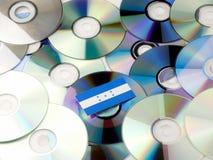 Honduras flag on top of CD and DVD pile on white. Honduras flag on top of CD and DVD pile stock photos