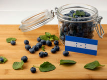 Honduras flag on a wooden plank with blueberries on whi. Te stock images