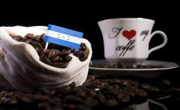 Honduras flagga i en påse med kaffebönor på svart Arkivfoton
