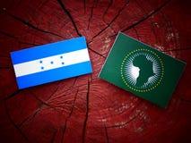 Honduras flagga med afrikanska unionenflaggan på en trädstubbe Arkivfoto