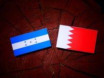 Honduras flagga med den bahrainska flaggan på en isolerad trädstubbe Royaltyfri Bild
