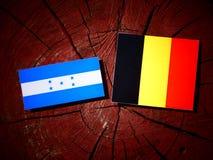 Honduras flagga med den belgiska flaggan på en isolerad trädstubbe Fotografering för Bildbyråer