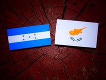 Honduras flagga med den cypriotiska flaggan på en isolerad trädstubbe Royaltyfri Bild