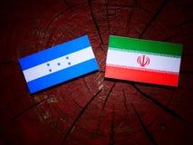 Honduras flagga med den iranska flaggan på en isolerad trädstubbe Arkivfoton