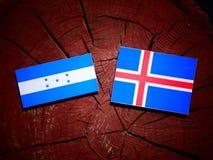 Honduras flagga med den isländska flaggan på en isolerad trädstubbe Arkivbild