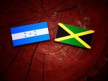 Honduras flagga med den jamaikanska flaggan på en trädstubbe Royaltyfria Foton