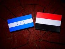Honduras flagga med den jemenitiska flaggan på en trädstubbe Royaltyfria Bilder