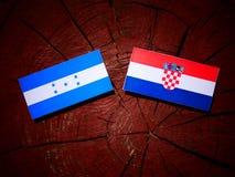 Honduras flagga med den kroatiska flaggan på en isolerad trädstubbe Royaltyfri Foto