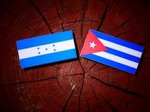 Honduras flagga med den kubanska flaggan på en isolerad trädstubbe Arkivbild