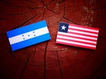 Honduras flagga med den liberianska flaggan på en isolerad trädstubbe Arkivfoto
