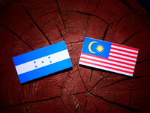 Honduras flagga med den malaysiska flaggan på en isolerad trädstubbe Arkivfoto