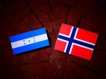 Honduras flagga med den norska flaggan på en isolerad trädstubbe Royaltyfri Fotografi
