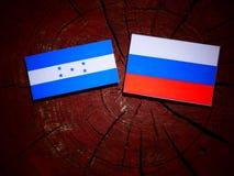 Honduras flagga med den ryska flaggan på en trädstubbe Fotografering för Bildbyråer