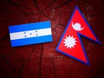 Honduras flagga med Nepaliflaggan på en isolerad trädstubbe Royaltyfri Foto