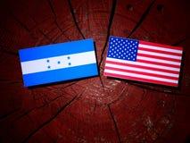 Honduras flagga med USA flaggan på en trädstubbe Royaltyfria Bilder