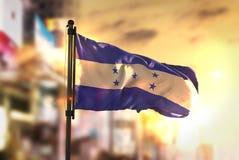 Honduras flagga mot suddig bakgrund för stad på soluppgång Backlig Royaltyfri Bild