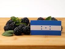Honduras flagga på en träpanel med björnbär som isoleras på a Arkivfoton