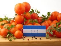 Honduras flagga på en träpanel med tomater som isoleras på en whit Arkivfoto
