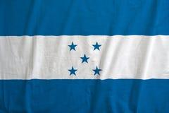 Honduras flagga på tygtexturen Arkivfoton