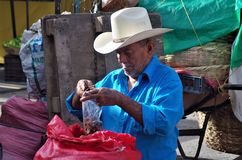 Man on a Honduras market packing tamarind for sale stock images