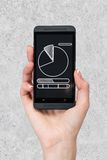 Hone with pie chart. Phone with pie chart in hand on gray background Royalty Free Stock Photos