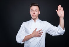 Honest cook rising his left hand and swearing Royalty Free Stock Images