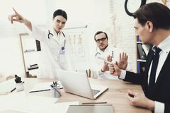 Honest doctor and nurse refuses to take bribe from patient in medical office. royalty free stock photo