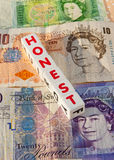 Honest money. Twenty, ten and one pound note Sterling, with text 'honest' in red uppercase letters inscribed on small white cubes  placed on top: concept of Stock Image