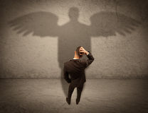 Honest salesman with angel shadow concept Stock Photography