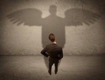 Honest salesman with angel shadow concept Stock Image