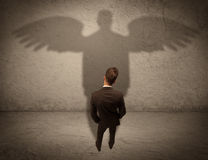 Honest salesman with angel shadow concept Royalty Free Stock Photography