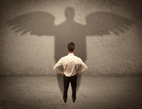 Honest salesman with angel shadow concept Royalty Free Stock Photo