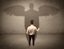 Honest salesman with angel shadow concept Royalty Free Stock Photos