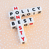 Honesty best policy. Text honesty best policy inscribed on small white cubes in uppercase letters arranged jigsaw style, bright dotted background Stock Photography
