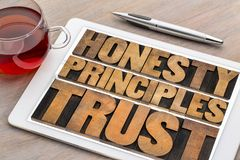 Honesty, principles and trust word abstract ontablet. Honesty, principles and trust concept - word abstract in vintage letterpress wood type on a digital tablet Stock Image