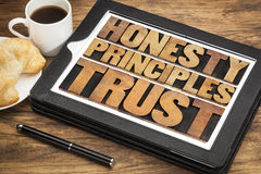 Honesty, principles and trust. Words in vintage letterpress wood type on a touchscreen of digital tablet with a cup of coffee royalty free stock photos
