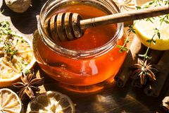 Honew. Honey jar with a wooden spoon and spices stock image