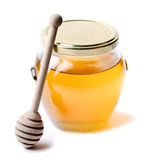 Honey. A jar of honey isolated on white background with wood stick Stock Photos
