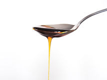 Honey. A spoon with honey poured Royalty Free Stock Image
