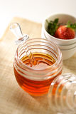 Honey. In a glass jar with wooden dripper on top Royalty Free Stock Photos