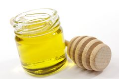 Honey. Jar of honey and wooden deeper Royalty Free Stock Photo