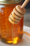Honey. Close up of a honey dipper with honey dripping from it Royalty Free Stock Image